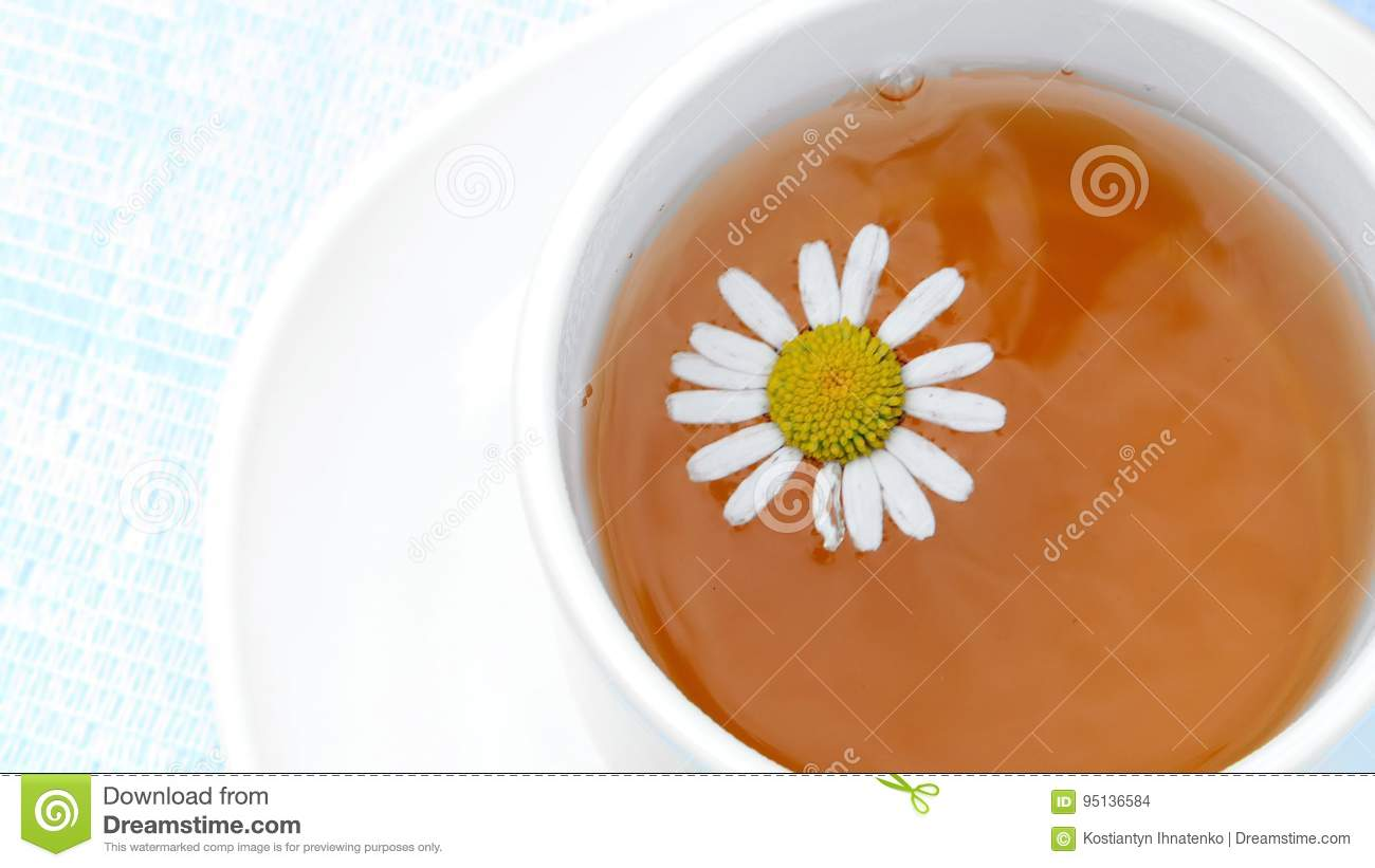 A Close Up A White Cup With Tea A Daisy Flower Floating On Top Of