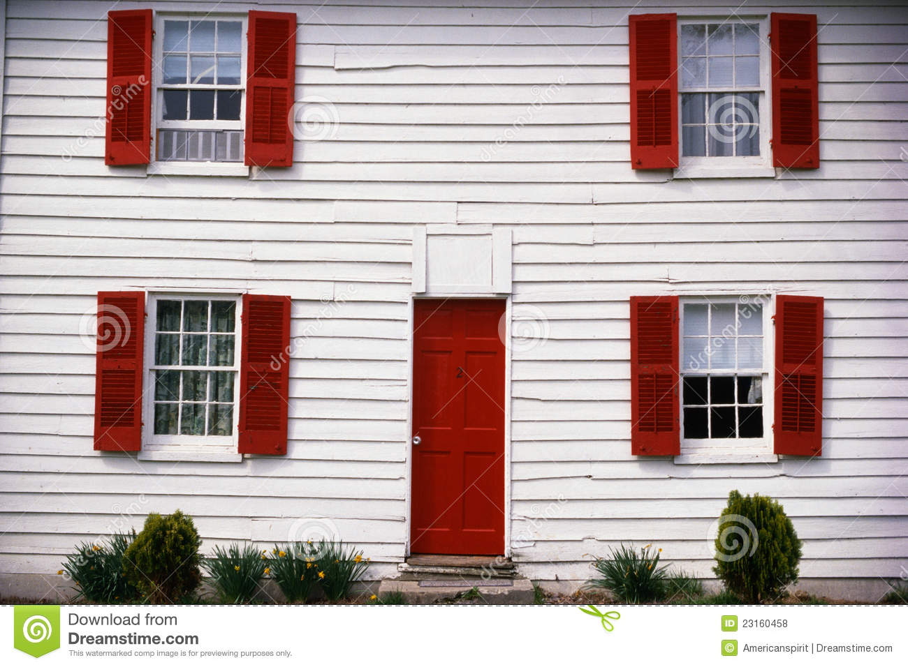 Close Up Of A White House With Red Shutters Stock Photo