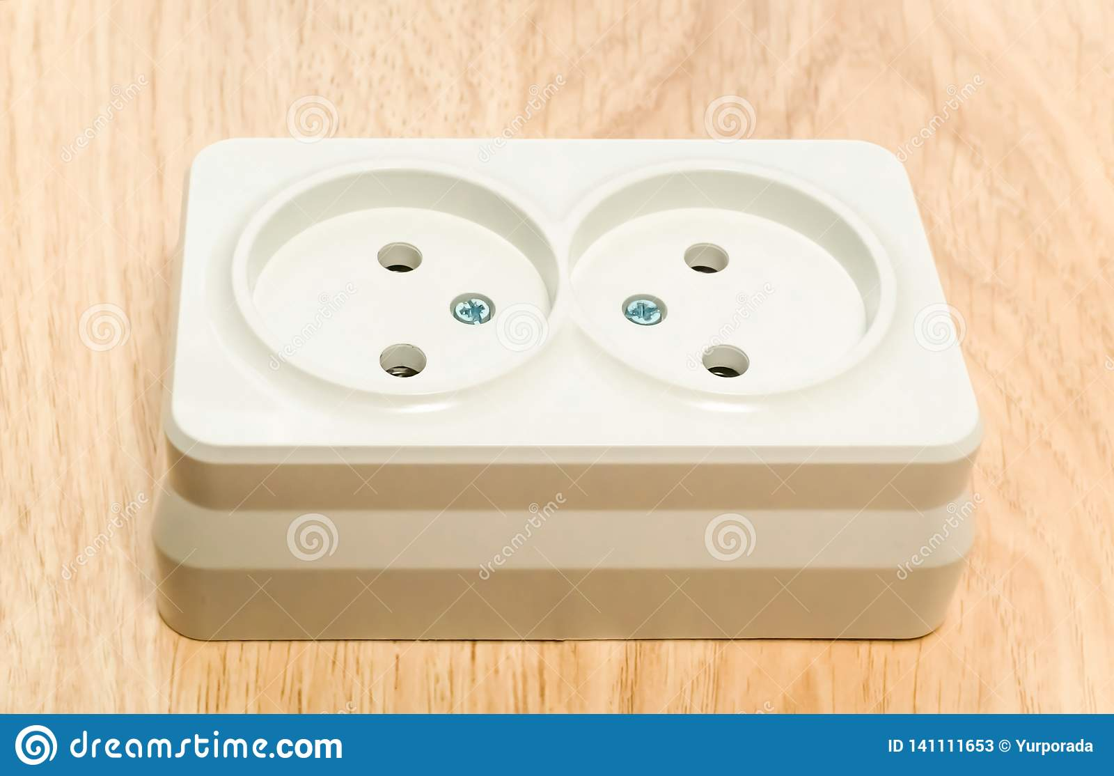 Close-up of a white outlet on a wooden table