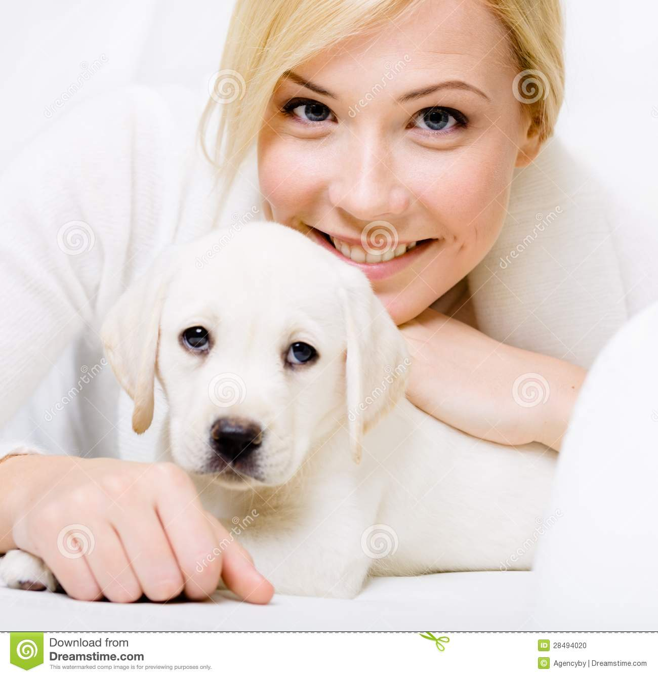 Close up of white puppy lying on the sofa with woman