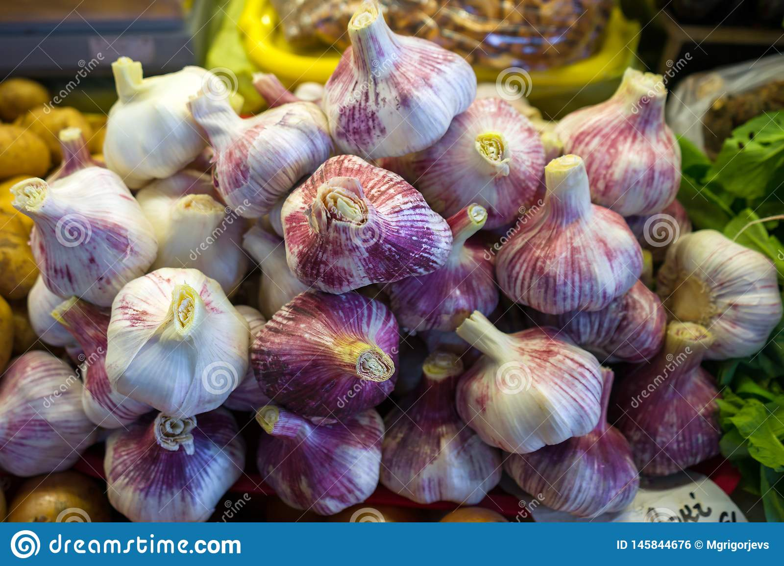 Close up of white and purple garlic bulbs on market stand for sale.