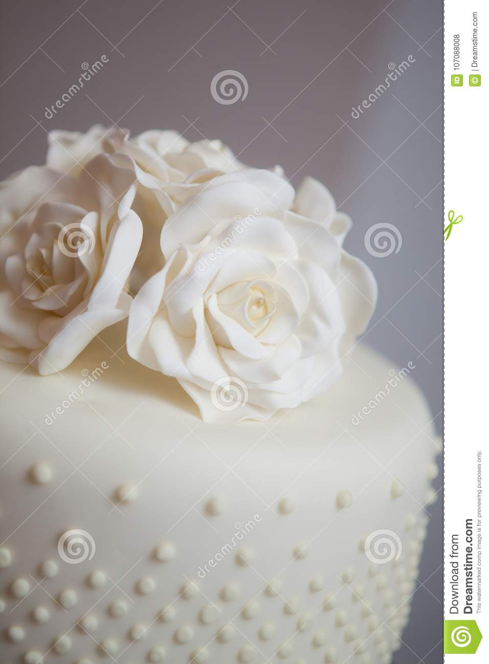 Close Up Of A White Wedding Cake With Flowers Decorating The Top