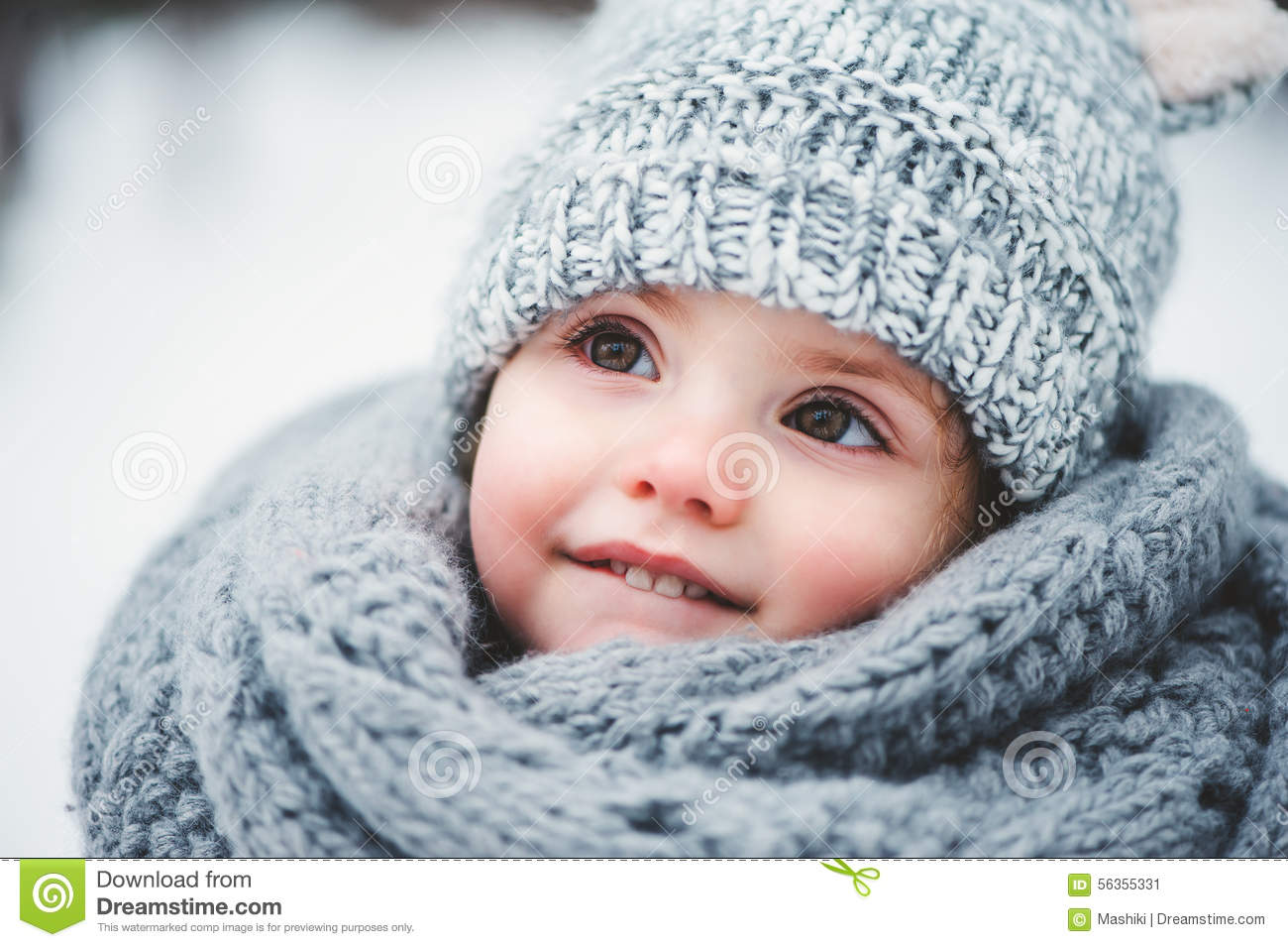 Close up winter portrait of adorable smiling baby girl in grey knitted hat  and scarf d2c085ef785