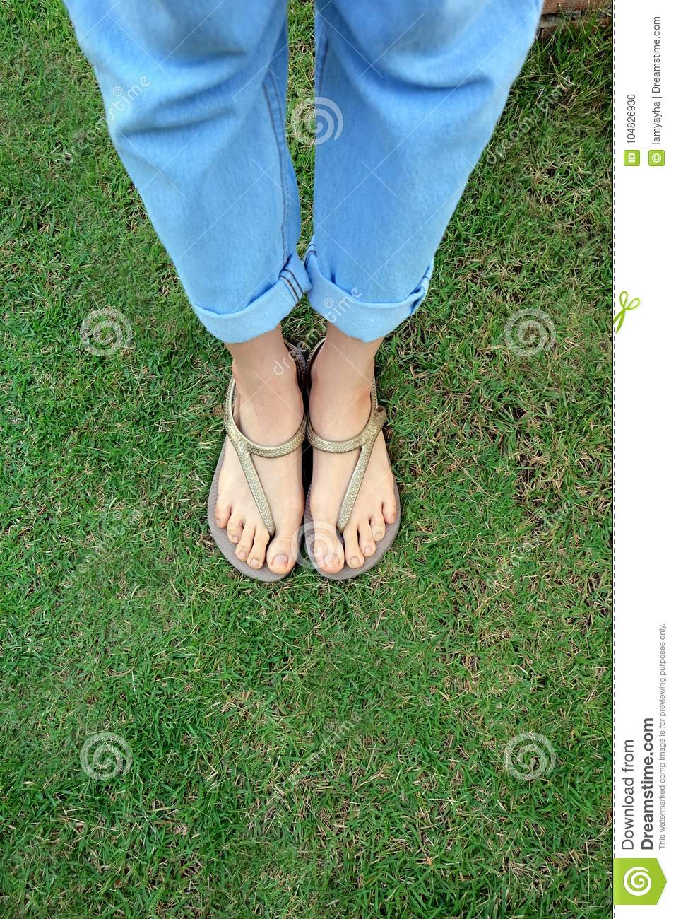 Close Up Woman's Legs and Feet Wearing Flip Flops on the Green Grass Background