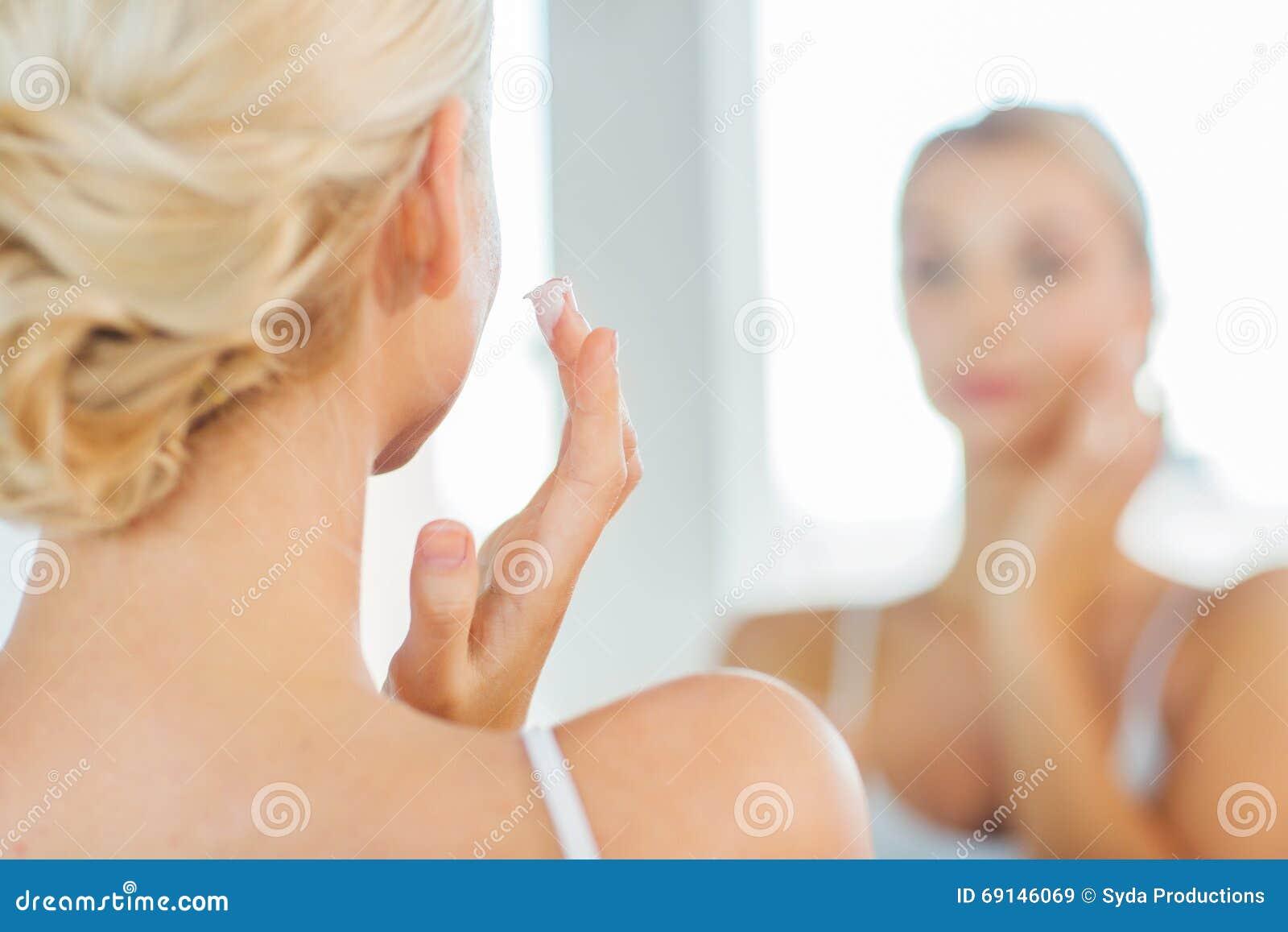 Close up of woman applying face cream at bathroom