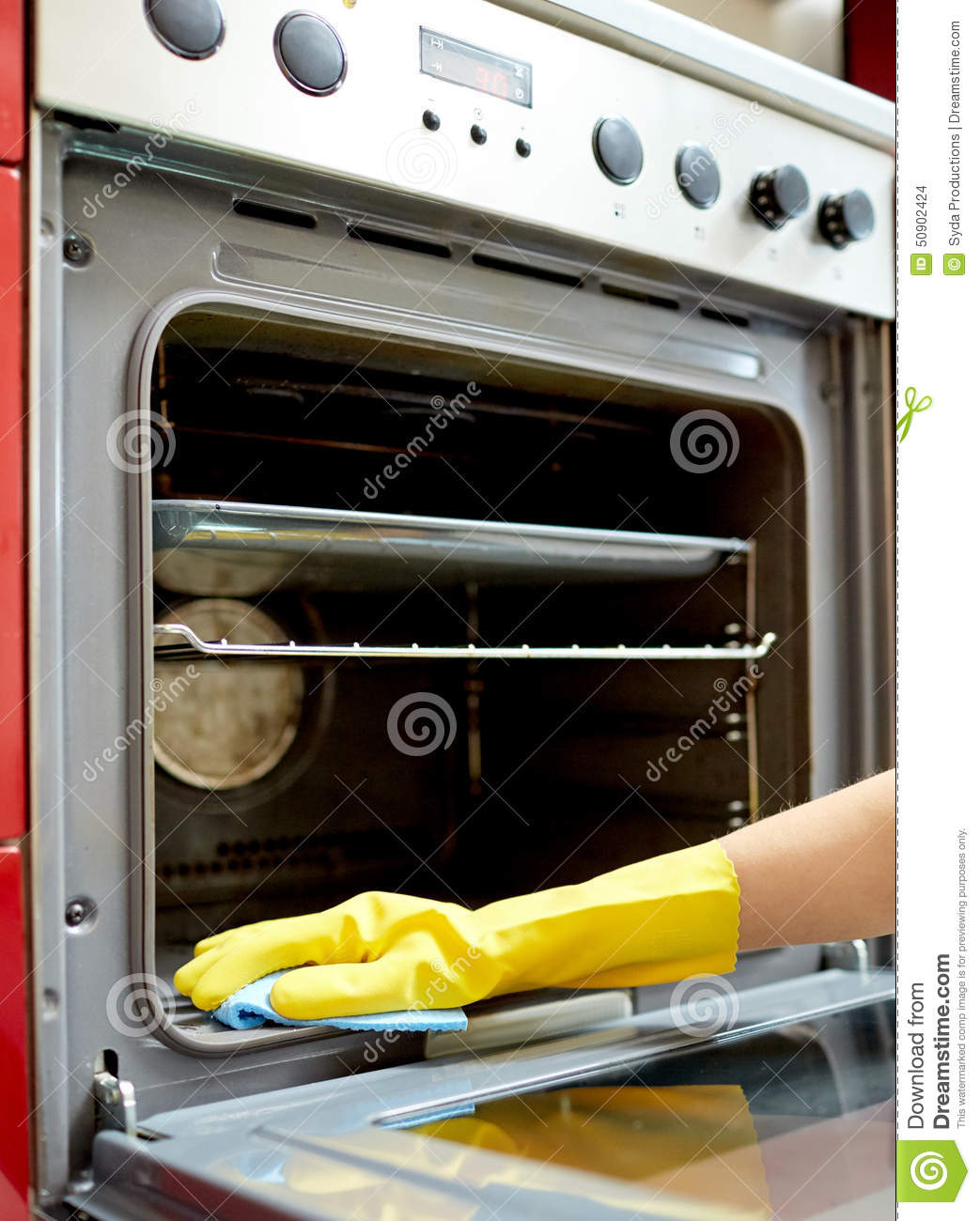 People Cleaning Kitchen: Close Up Of Woman Cleaning Oven At Home Kitchen Stock
