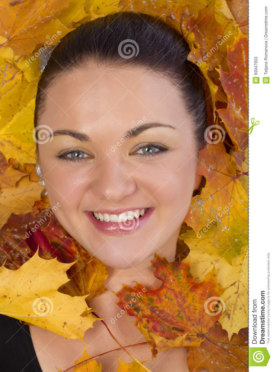Close up of woman face in autumn leaves