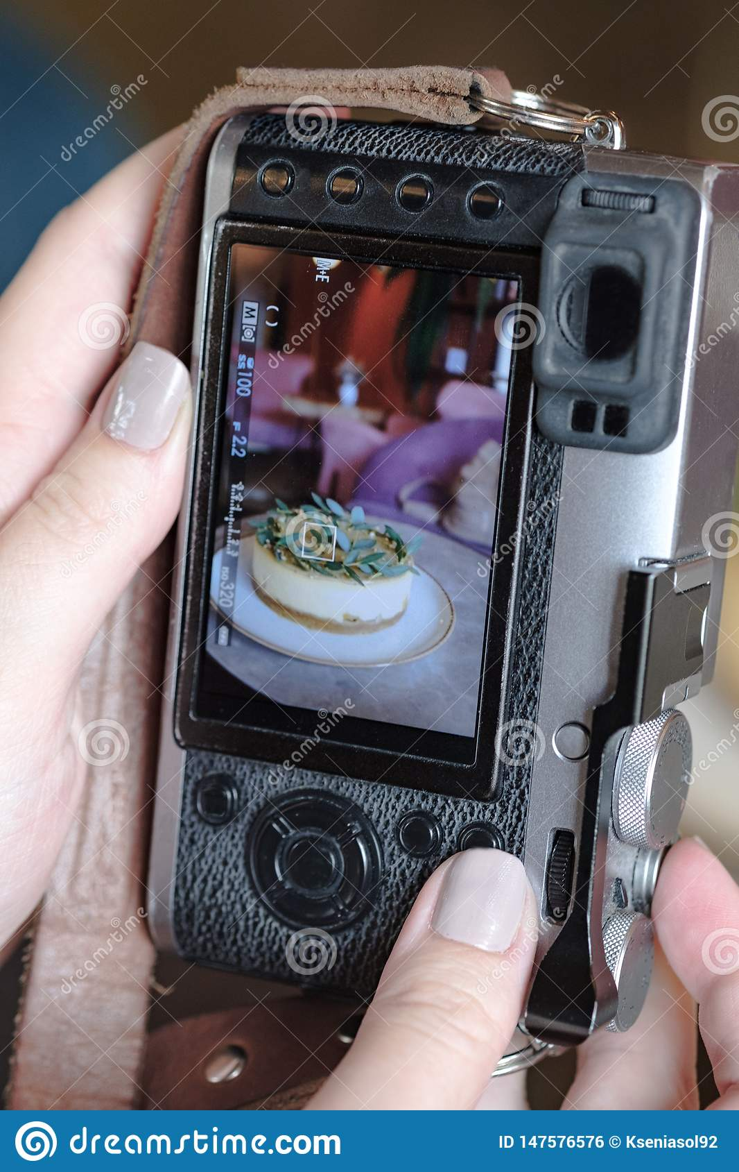A woman takes a photograph of the cake using a mirrorless camera