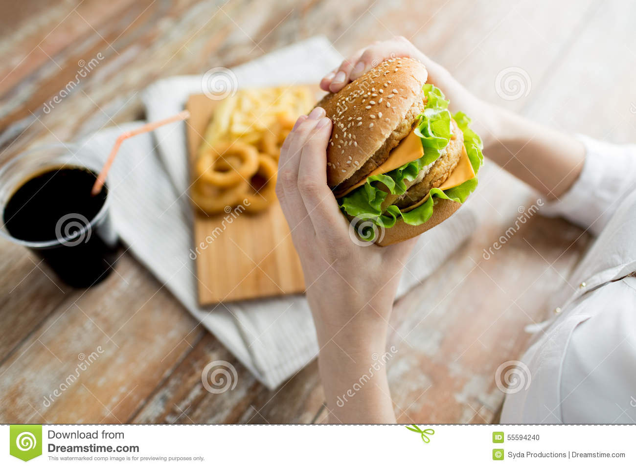 Close up of woman hands holding hamburger stock photo for Cuisine you eat with your hands