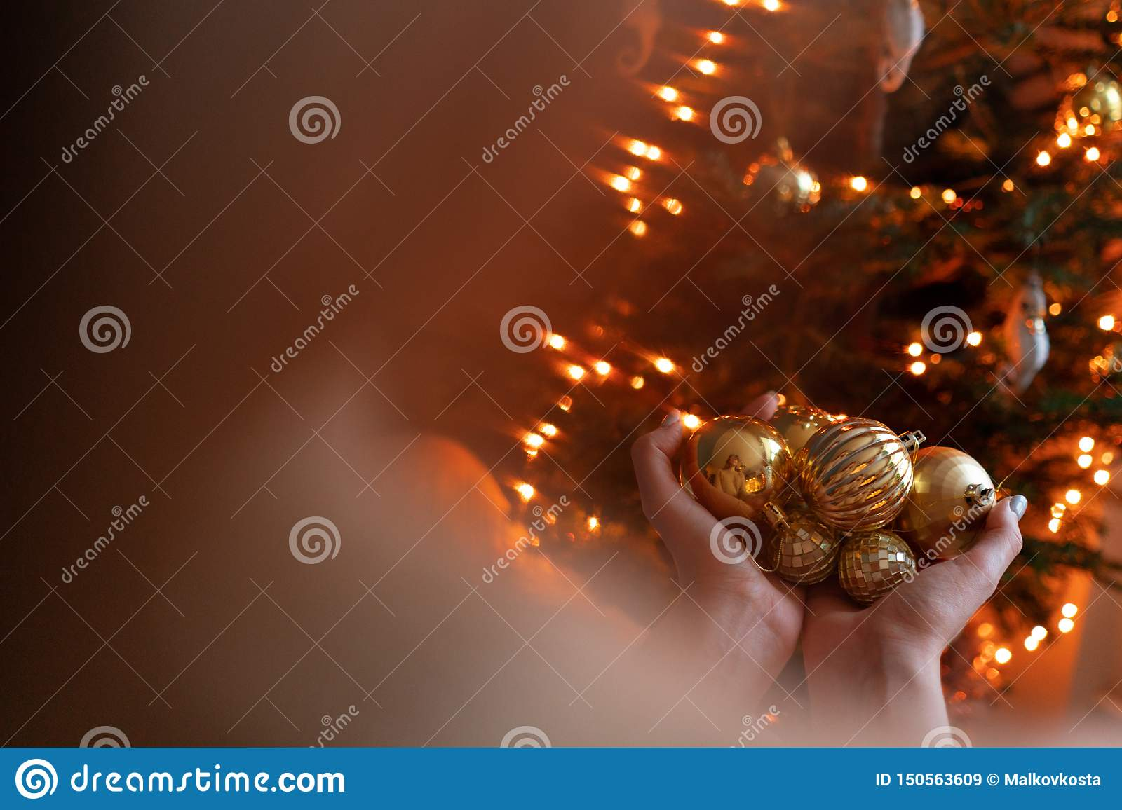 Close-up woman holds in the hands of Golden Christmas tree toys. Winter holidays in a house interior. Golden and white