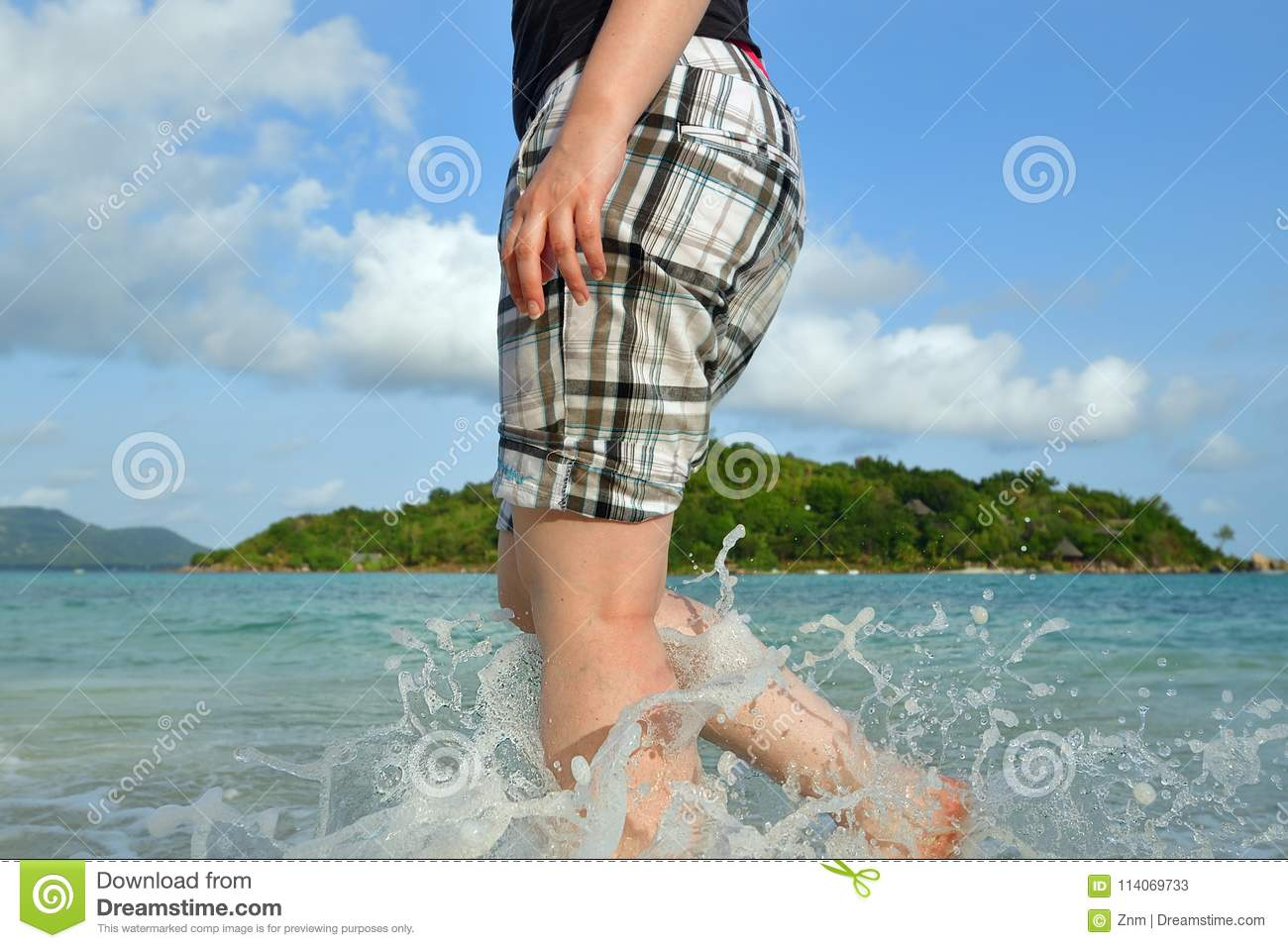 00af4c642c Woman barefoot walking on the beach at sunset. Close up leg of young woman  walking along wave of sea water tropical island on background. Travel  Concept