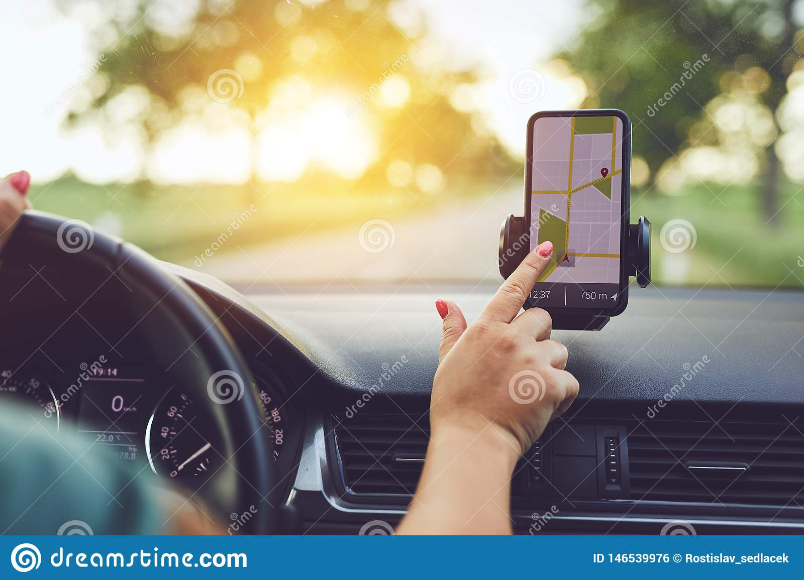 Woman using GPS navigation in mobile phone while driving car at sunset