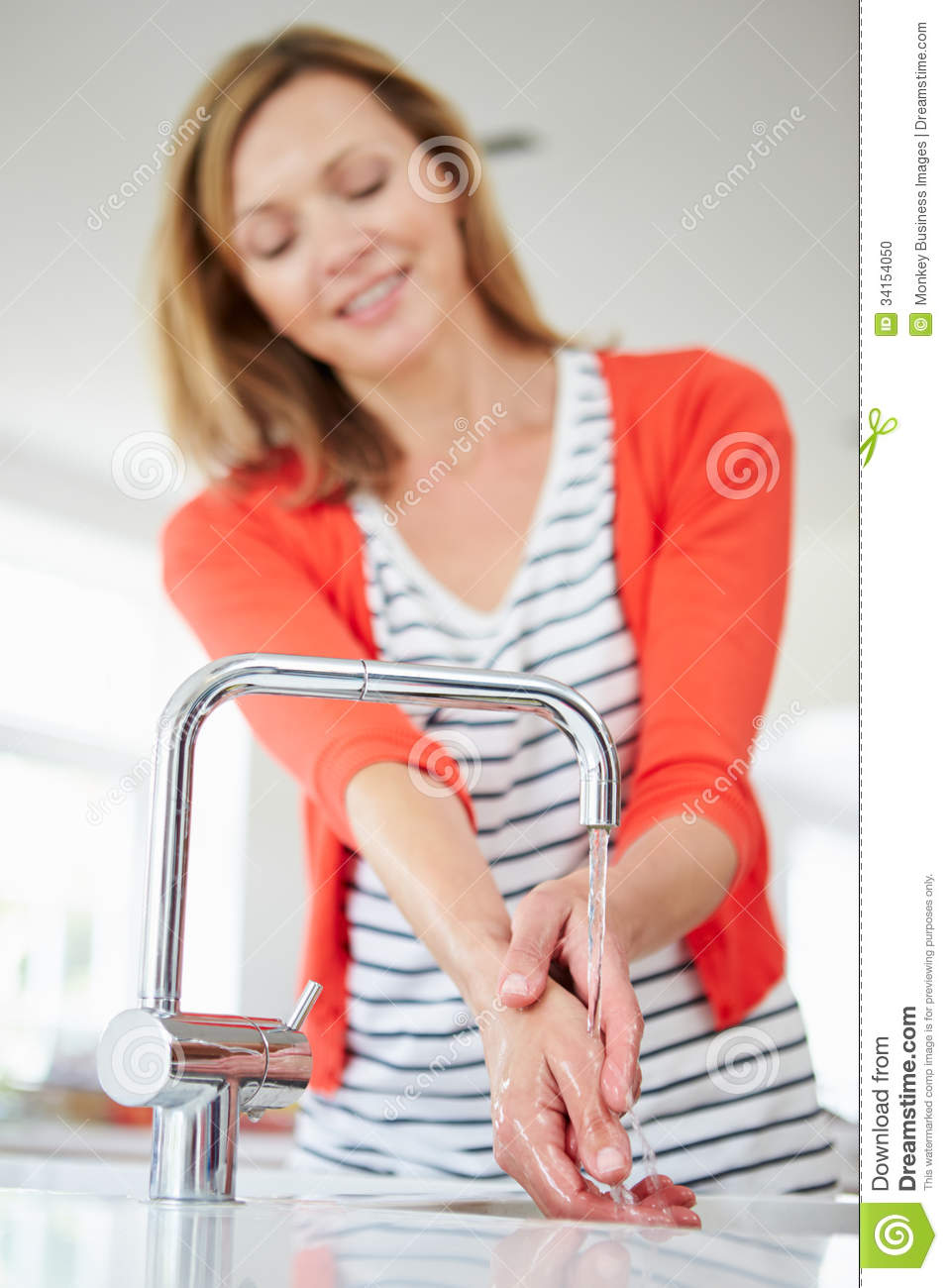 Close Up Of Woman Washing Hands In Kitchen Sink Stock