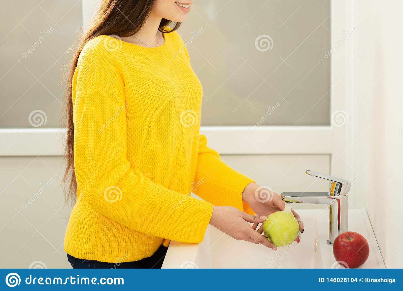 Close up of women`s hands washing green apple in sink