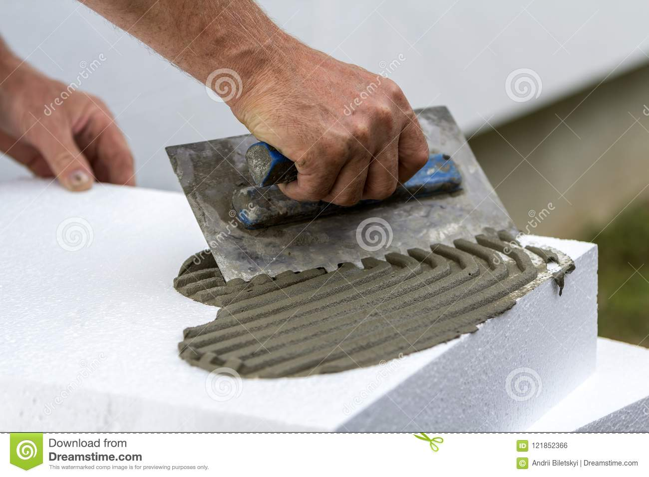 Close-up of worker hand with trowel applying glue on white rigid polyurethane foam sheet for house insulation. Modern technology,