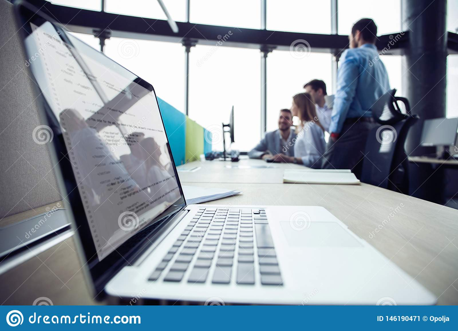 Close-up of workplace in modern office with business people behind. Colleagues meeting to discuss their future financial