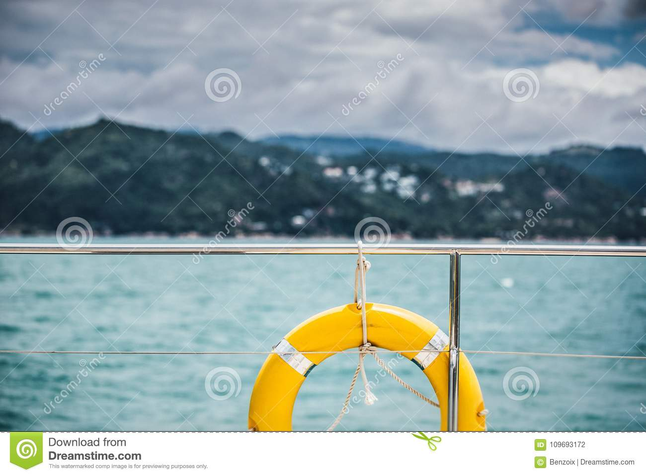 Close-up Yellow life ring hanging on boat with ocean background.