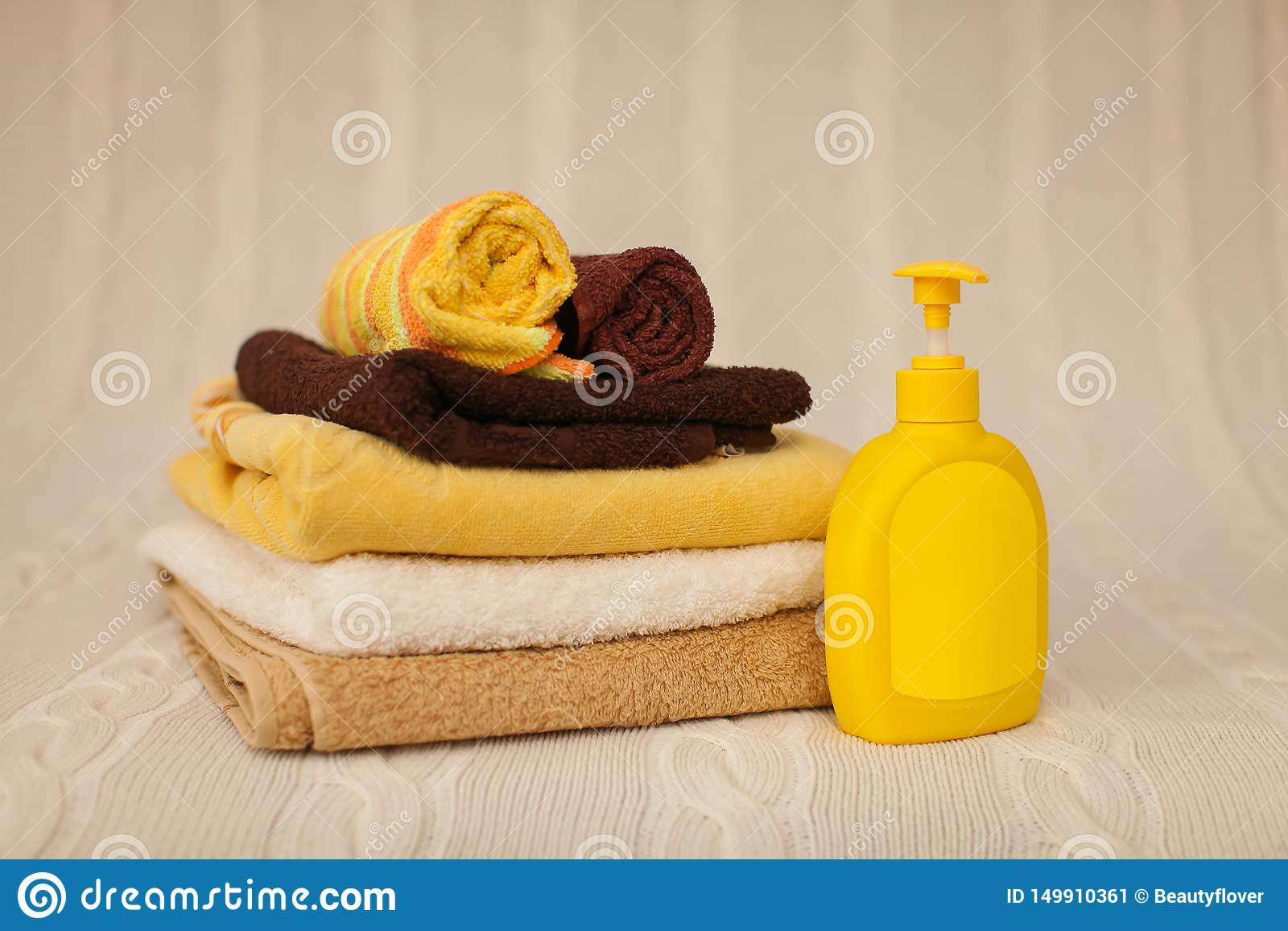 Yellow plastic dispenser with liquid soap and a stack of brown towels on a beige rug in selective focus