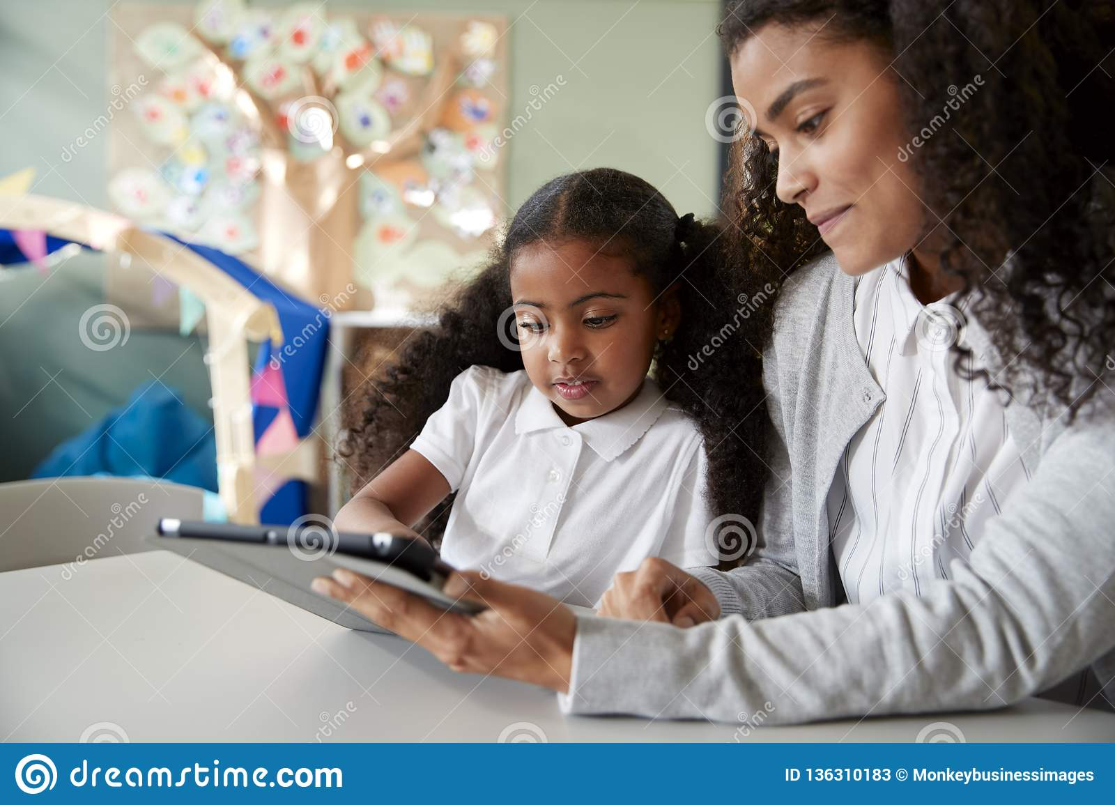 Close up of a young black schoolgirl sitting at a table in an infant school classroom learning one on one with a female teacher us