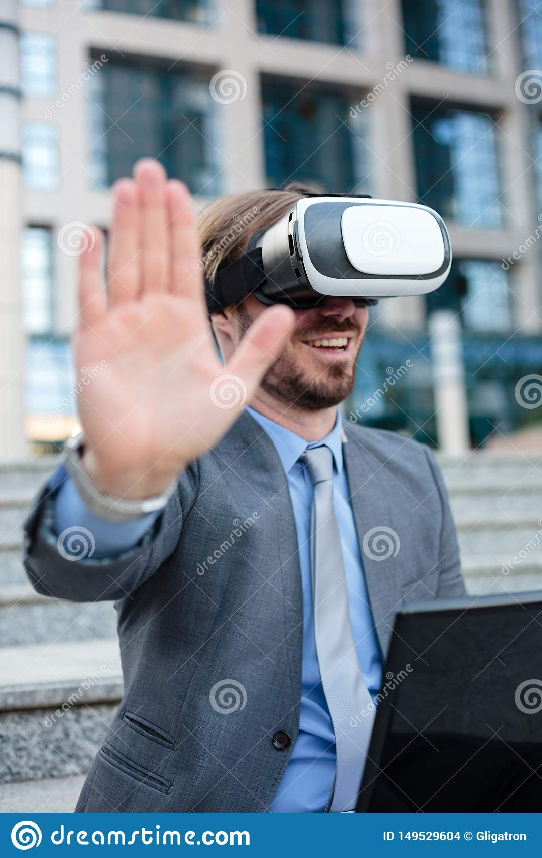 Close up of a young businessman using VR goggles in front of an office building. Selective focus concept, focus on head