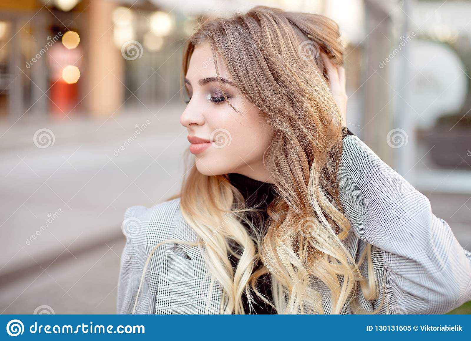 Close-up young fashion woman with shopping bags standing near storefront shop windows on the street outdoors