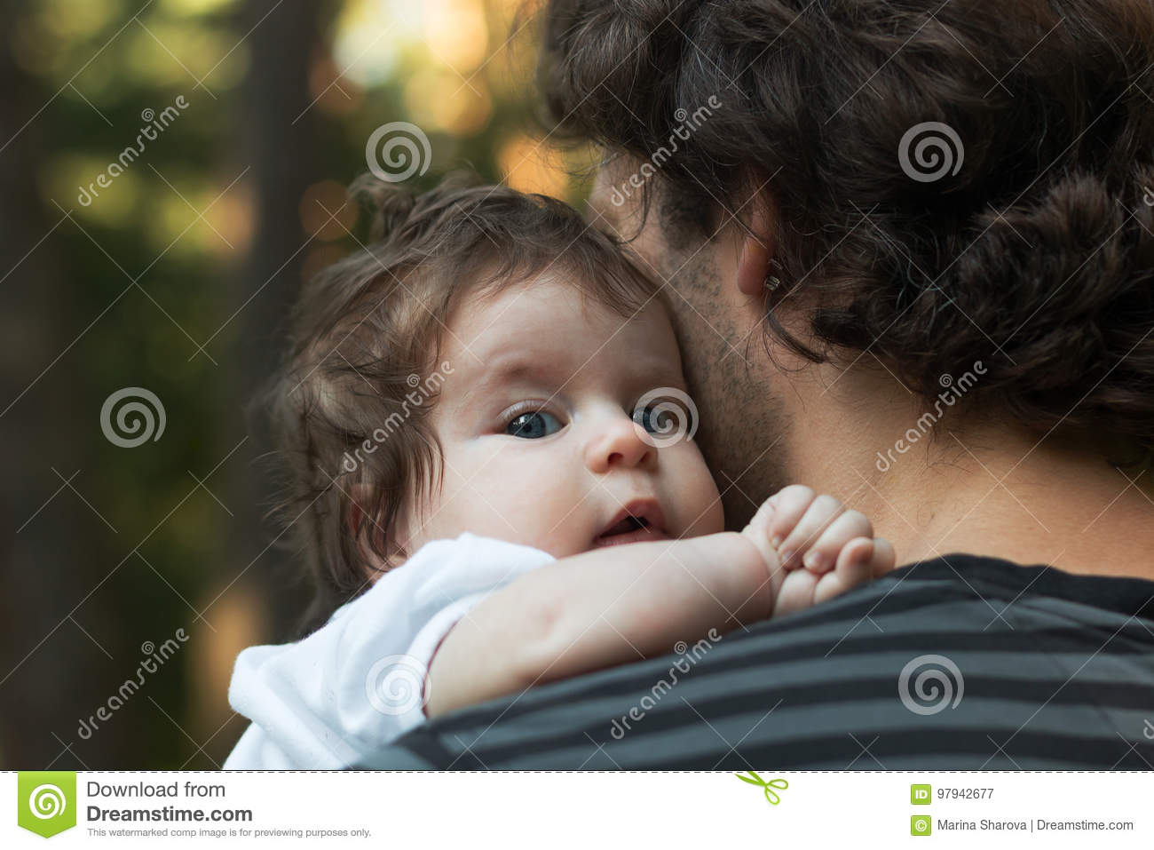 Close up of young father holding his newborn baby. Focus on the baby`s blue eyes