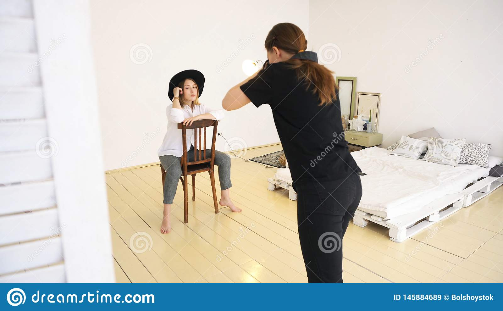 Close-up of young female photographer in black clothes taking pfotos of stylish young woman in black hat, white shirt