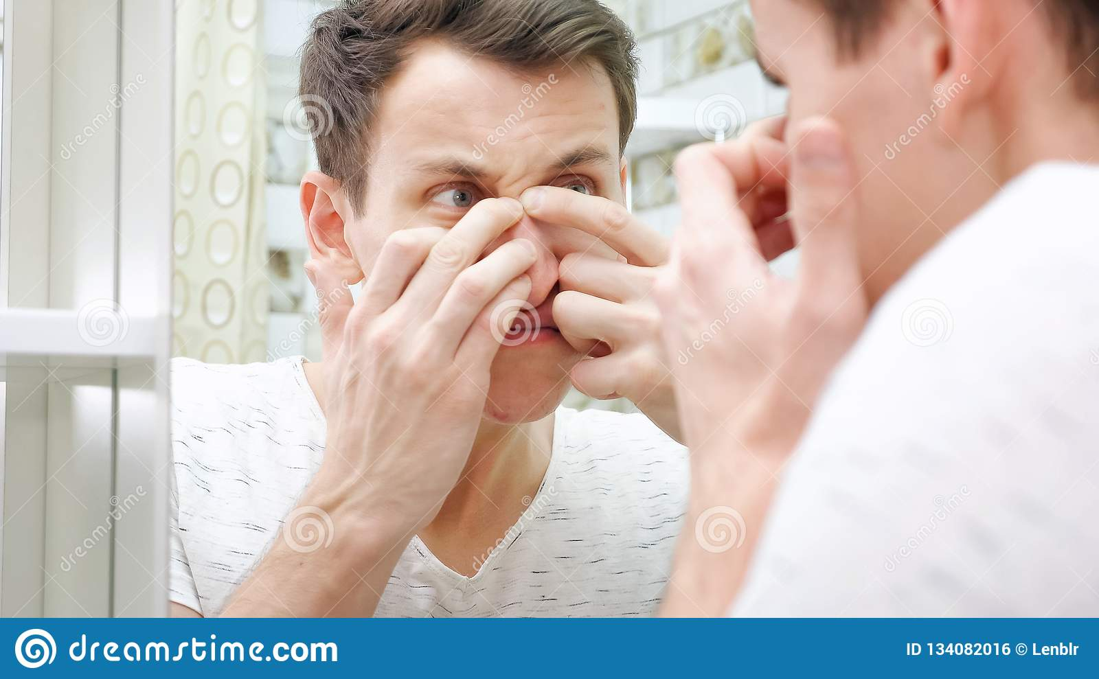 Close up of young man standing close to a mirror in the bathroom and squeezing a pimple on his face