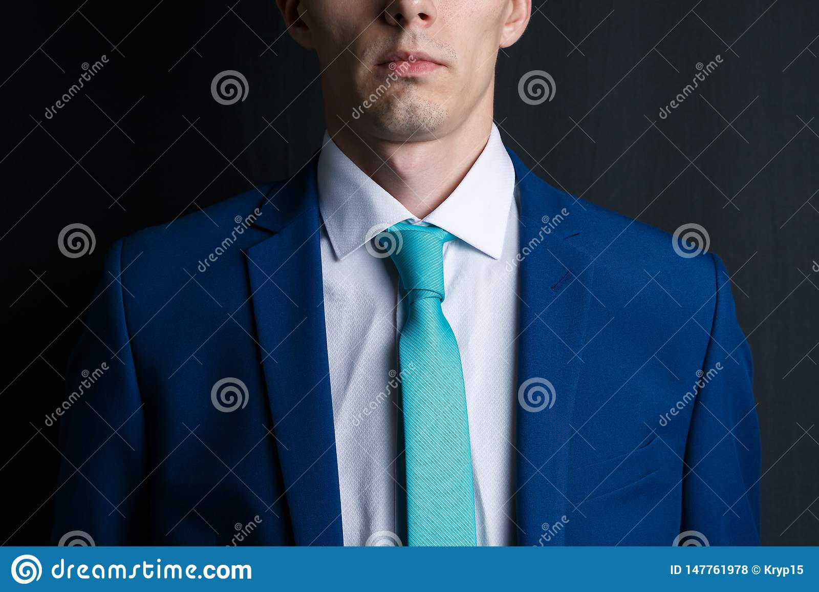 Close-up young man in an suit. He is in a white shirt with a tie. His face unshaven