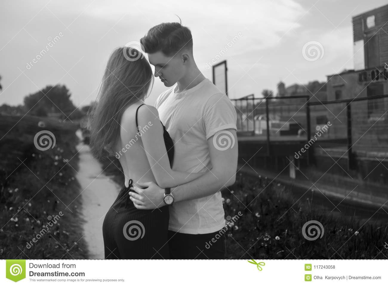 Close up of young romantic couple is kissing and enjoying the company of each other in black and white young couple in love hug each other girl in black