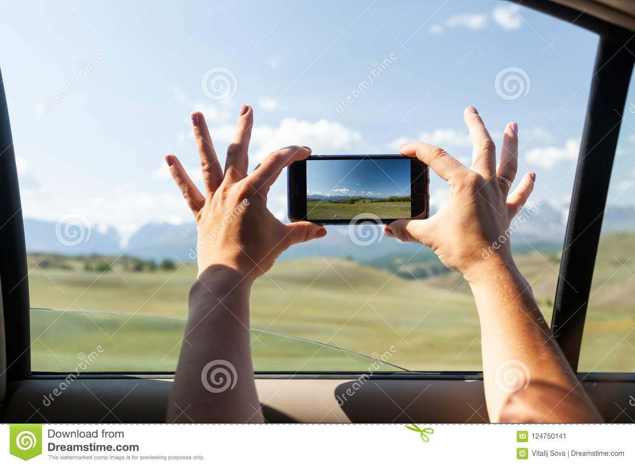 Close-up of a young tourist in car makes a photo