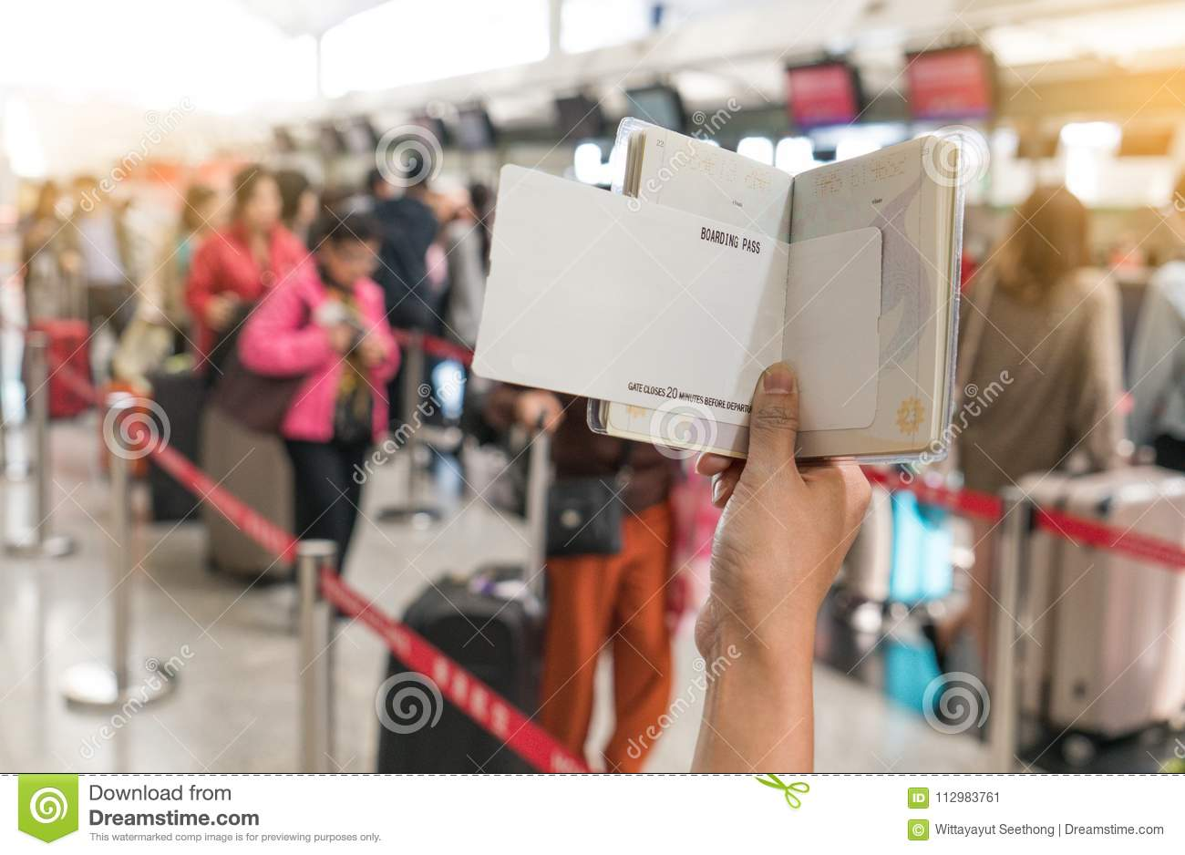 Close up of young woman holding passport and blank boarding pass at airport counters reception area with many people in background