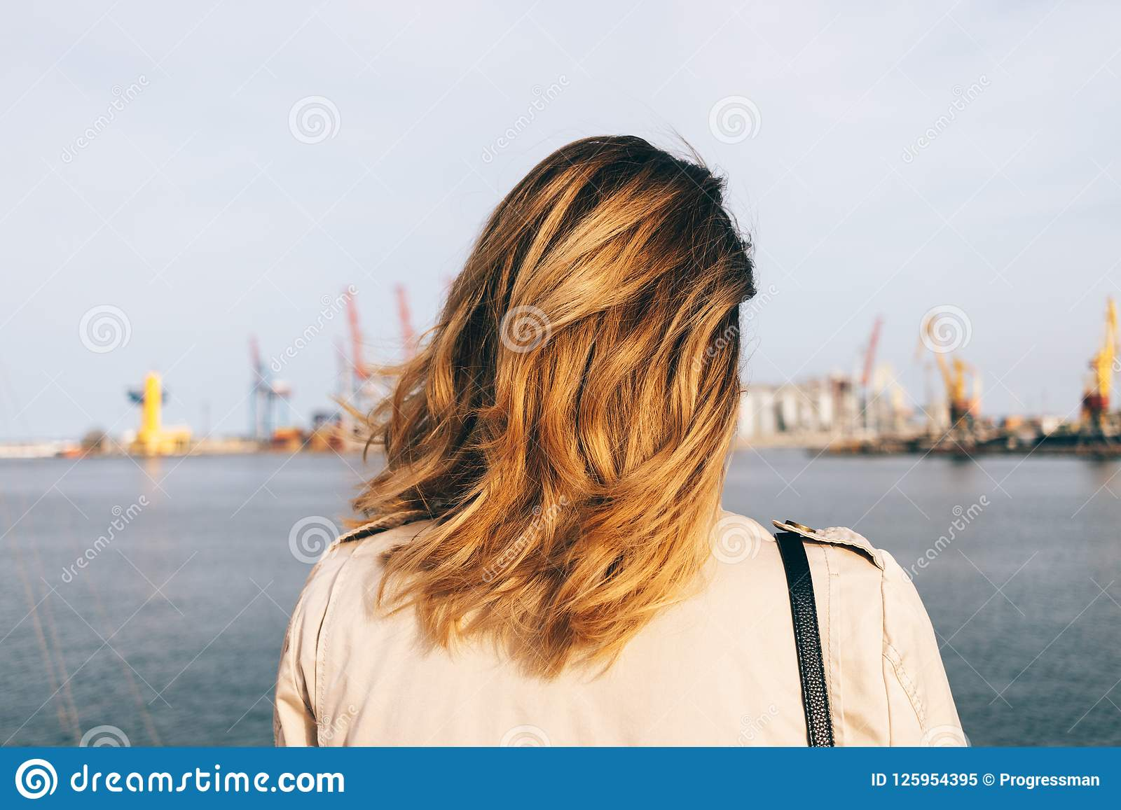 Close-up young woman looking at sea port standing on embankment