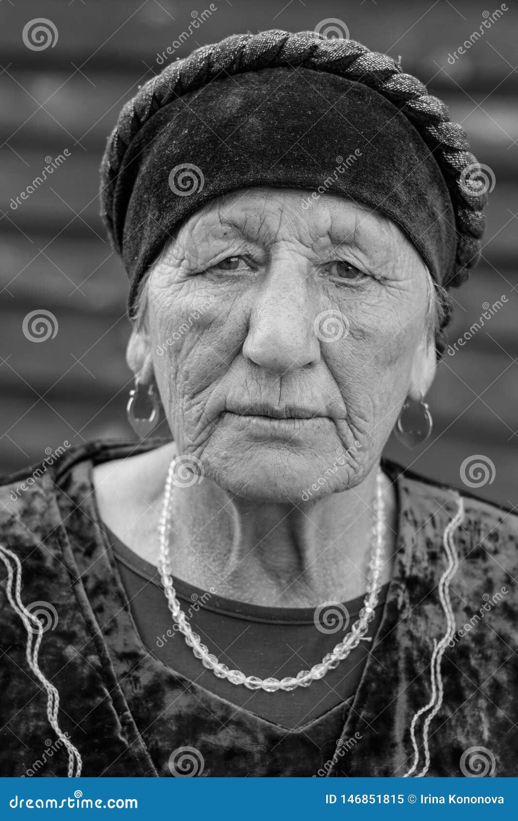 Close-up zwart-wit portret van een dorpsbejaarde in een nationaal kostuum