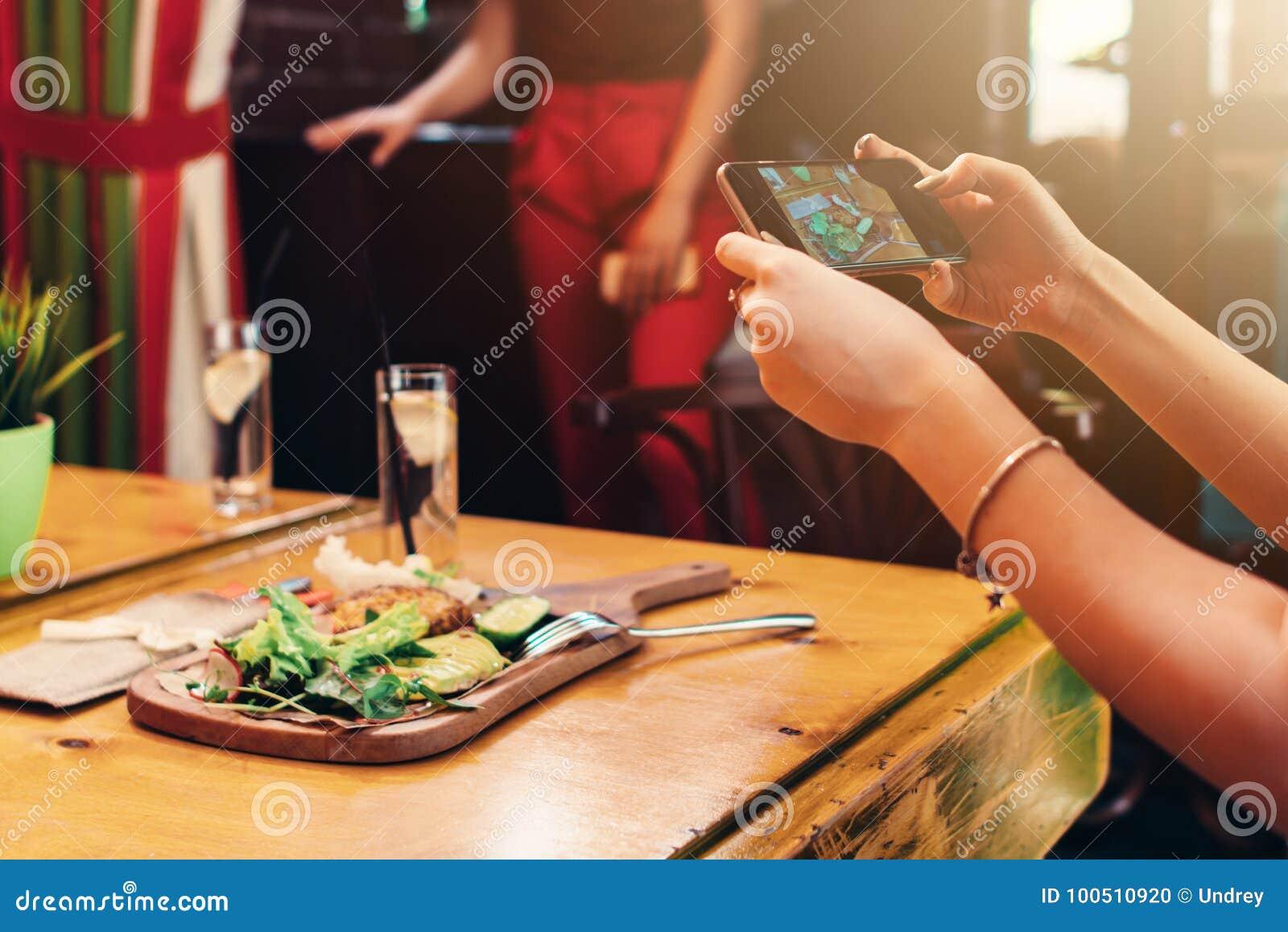 Close-upbeeld die van vrouwelijke handen een mobiele telefoon houden die beeld van gezonde heerlijke schotel in koffie nemen