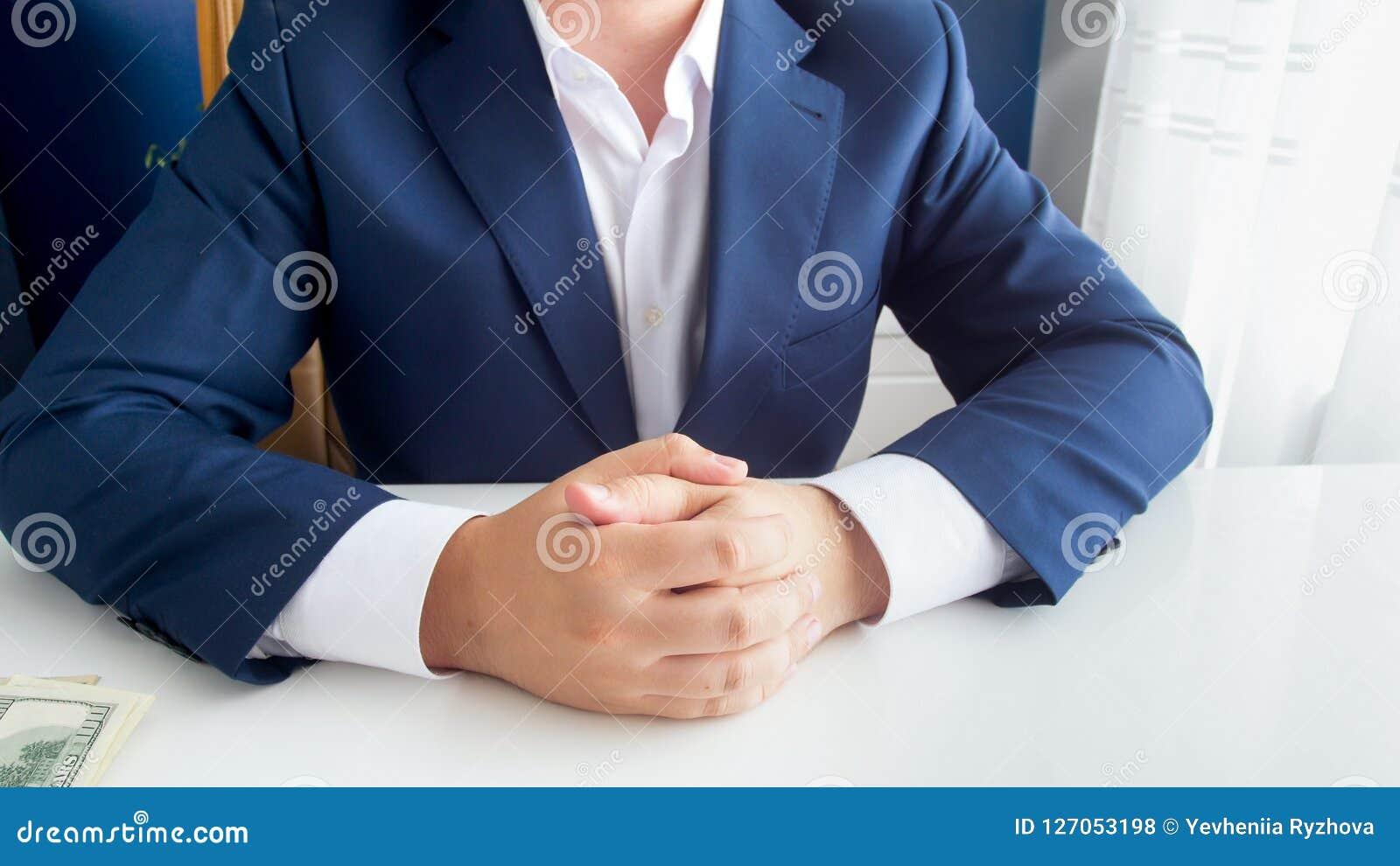 Close-upbeeld van rijke succesvolle zakenman in blauwe kostuumzitting met gevouwen handen op modern kantoor