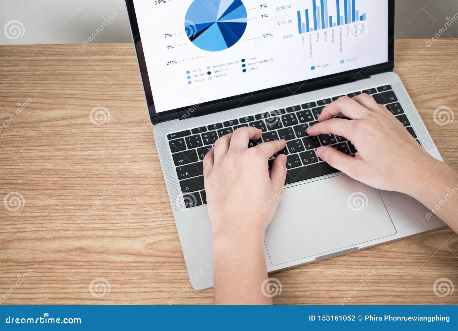 Close-upbeelden van handen op laptops die financi?le grafieken op het scherm op een bruine houten lijst tonen