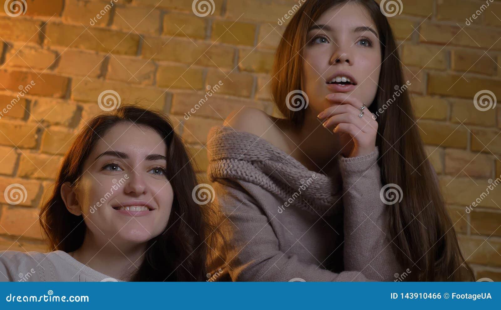 Close-upbottom up portret van twee jonge mooie vrouwen die op TV met opwinding in een comfortabele flat binnen letten