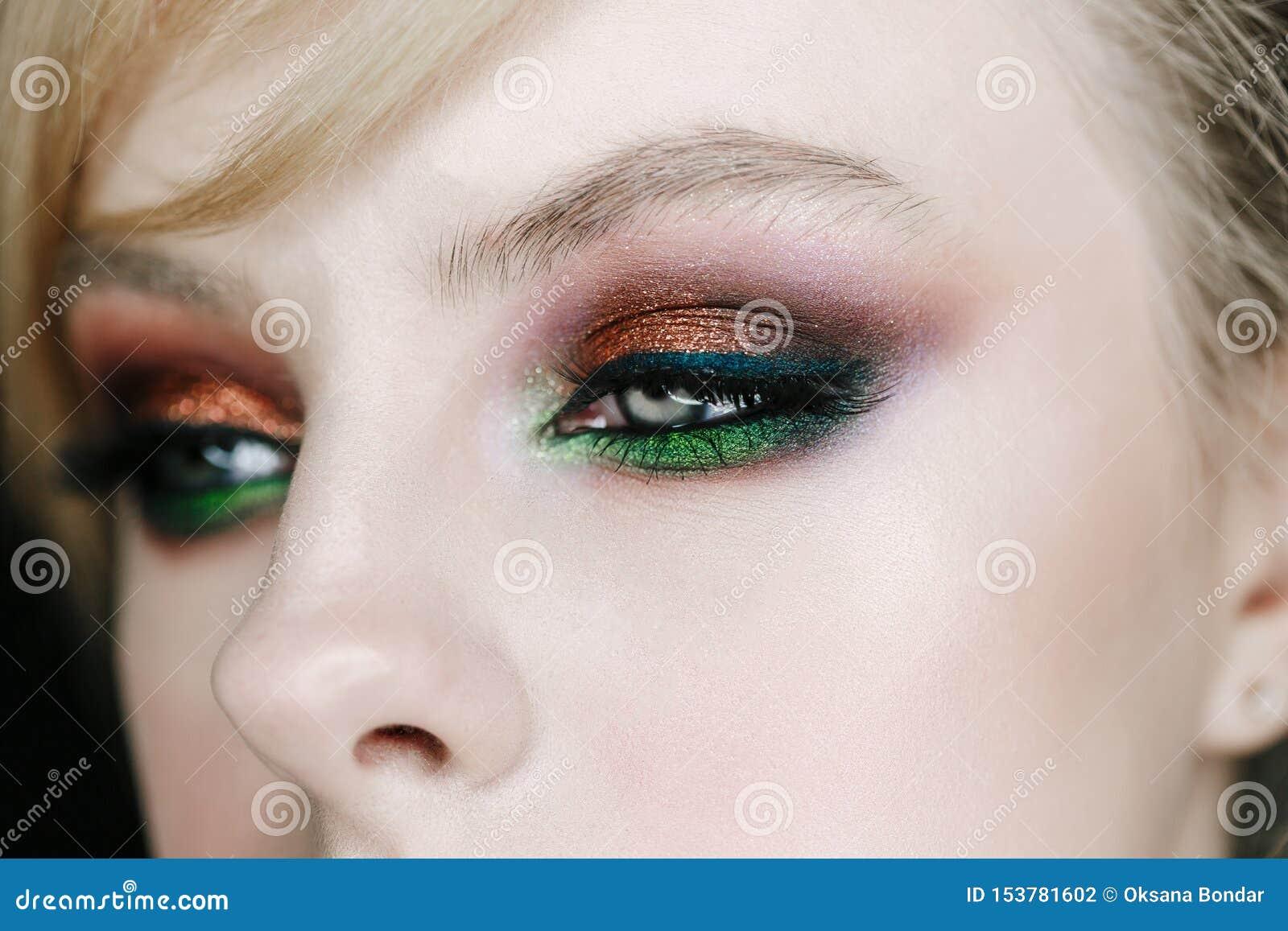 Close-upfoto van geopend vrouwenoog met mooie heldere make-up, bruine en groene rokerige ogen die rechterkant kijken