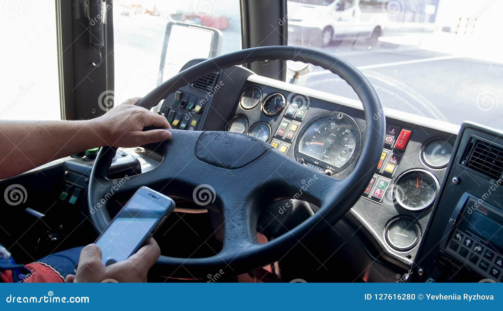 Close-upfoto van vrachtwagenchauffeur het typen op smartphone terwijl het drijven Gevaar in vervoer Onverantwoordelijke bestuurde