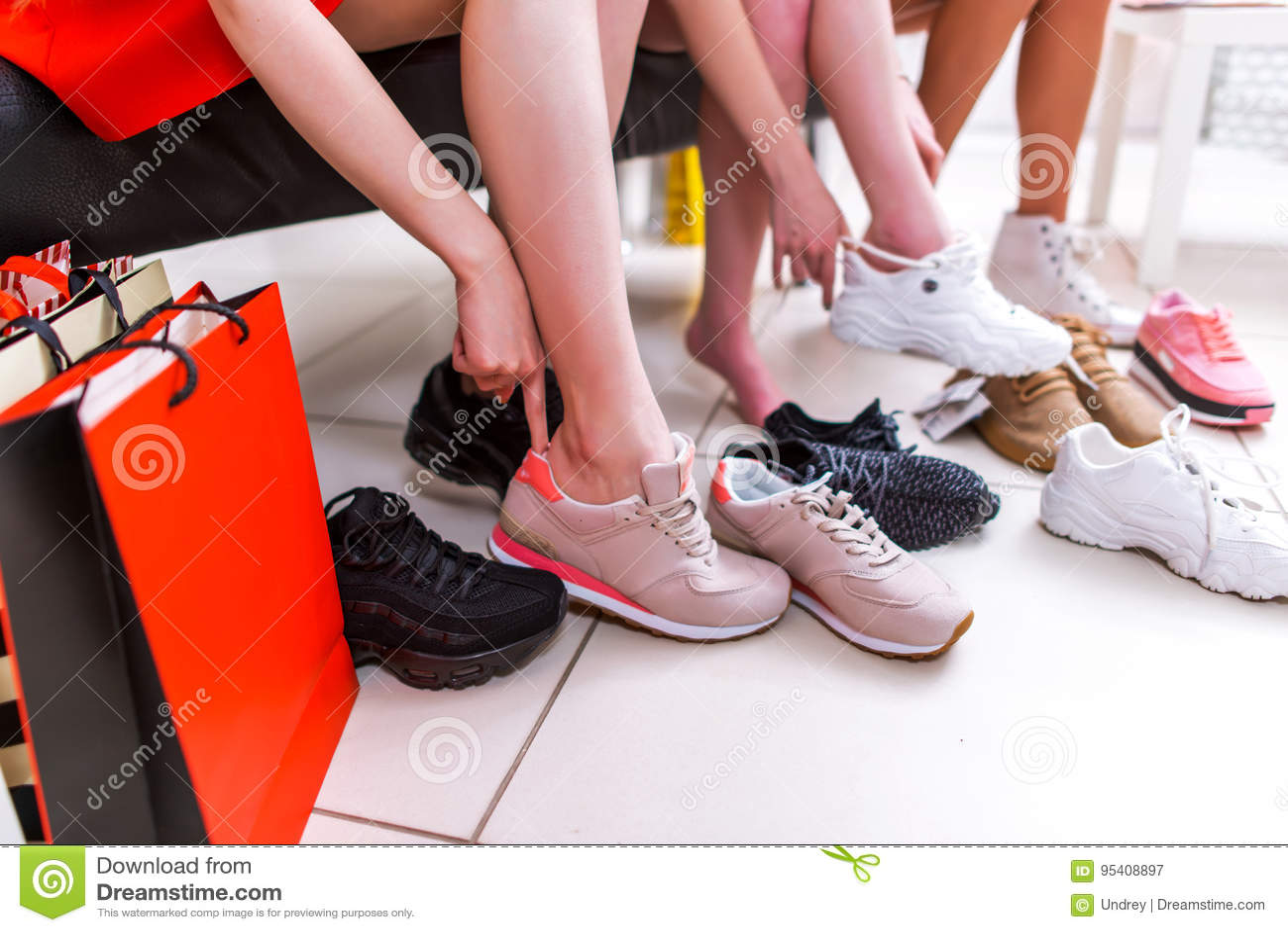 Close-upfoto van vrouwelijke benen die sportschoeisel kiezen die op verschillende tennisschoenen in een winkelcomplex proberen