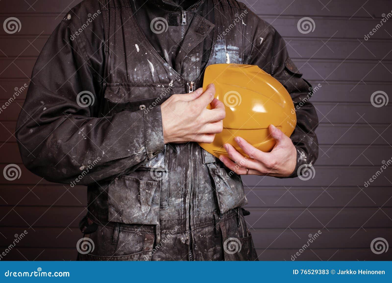 Close-upfoto van vuile laborer& x27; s overall en een gele veiligheidshelm