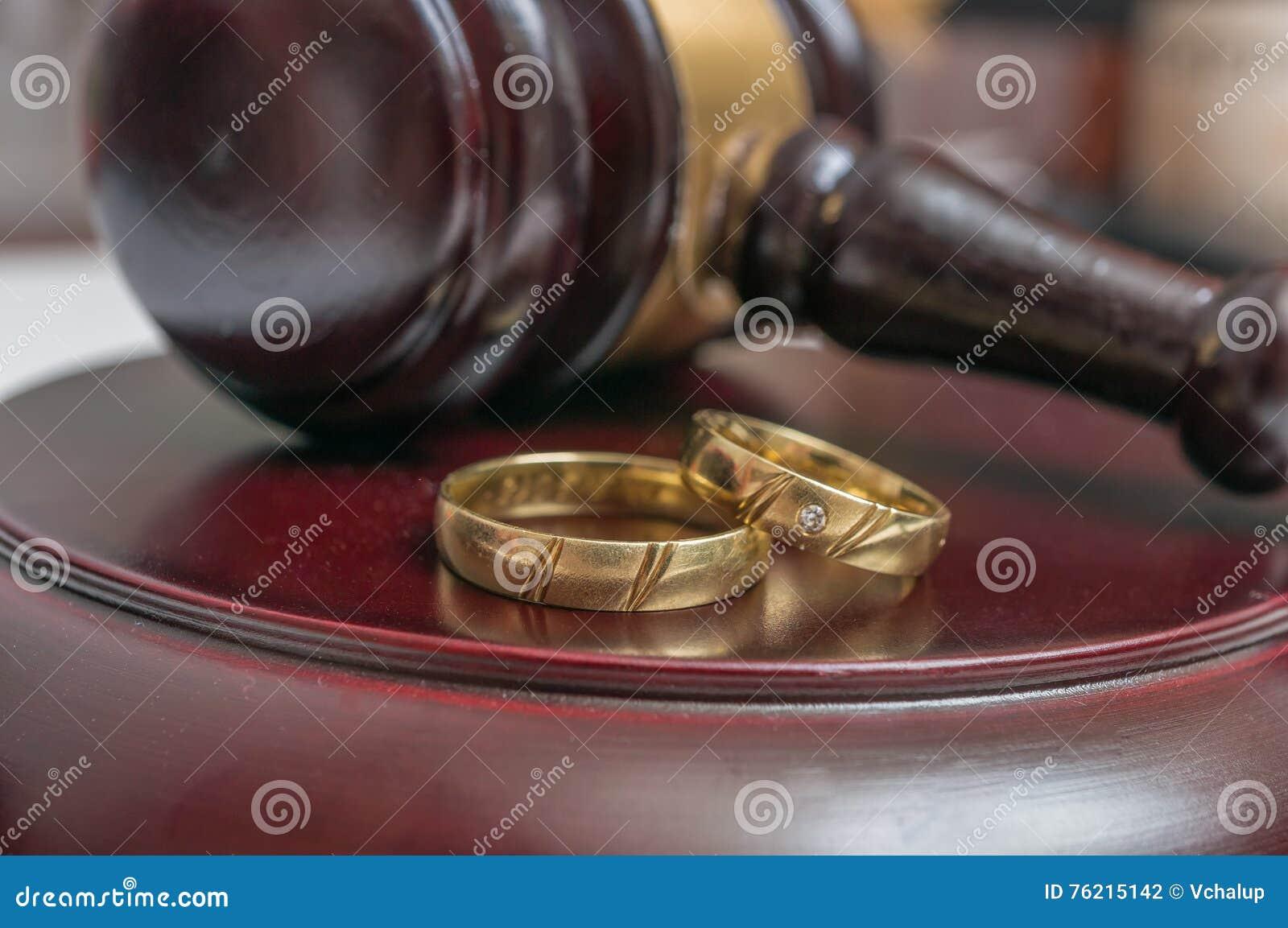 Close-upmening over gouden ringen en hamer op achtergrond Scheidingsconcept