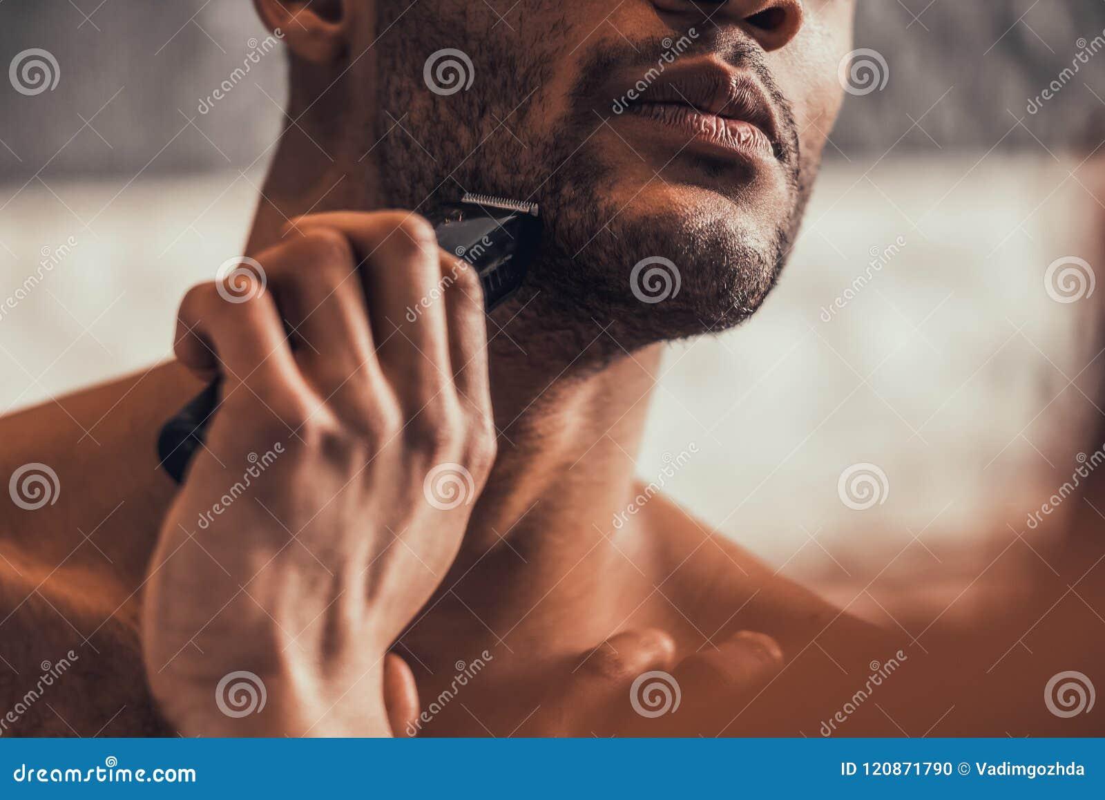 Close upp Afro--amerikan man som rakar i badrum