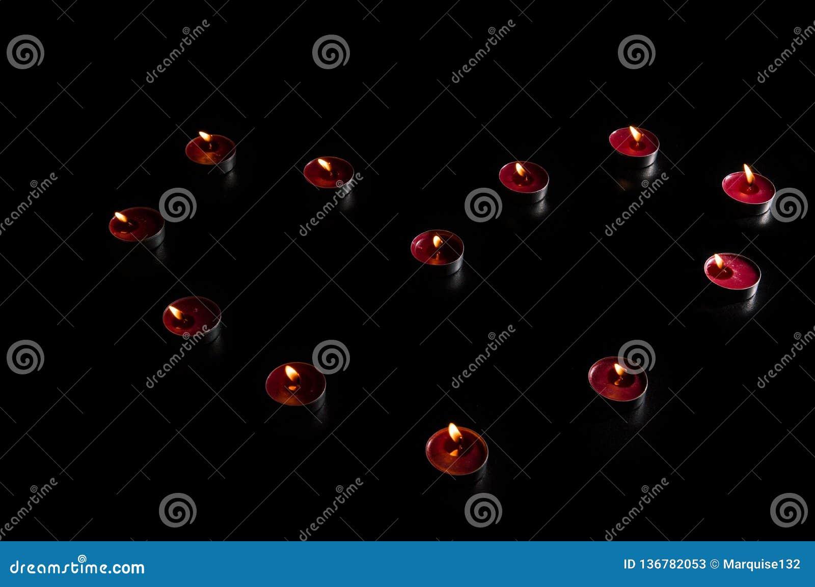 Close upp Beröm för dag för valentin` s Röda brinnande stearinljus lade ut i formen av en hjärta Svart bakgrund, låg tangent