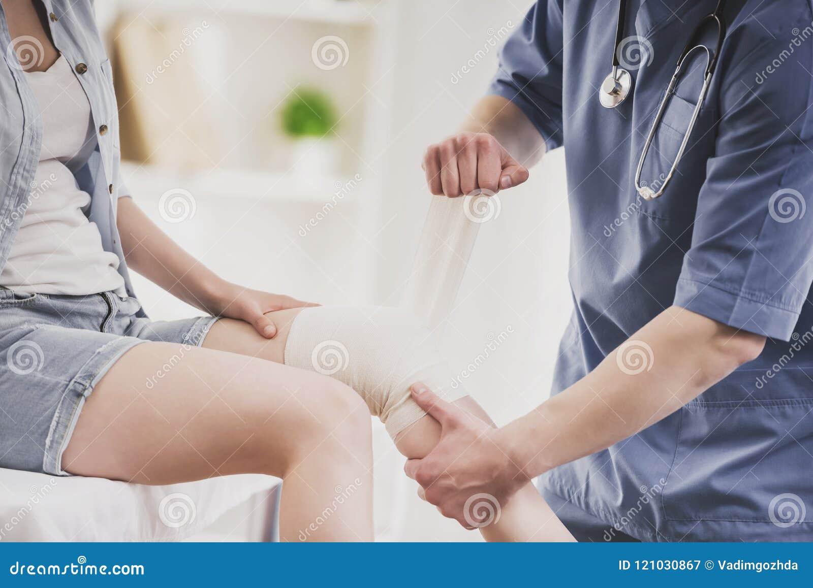 Close upp Doktor Comfforting Leg av sammanträdekvinnan