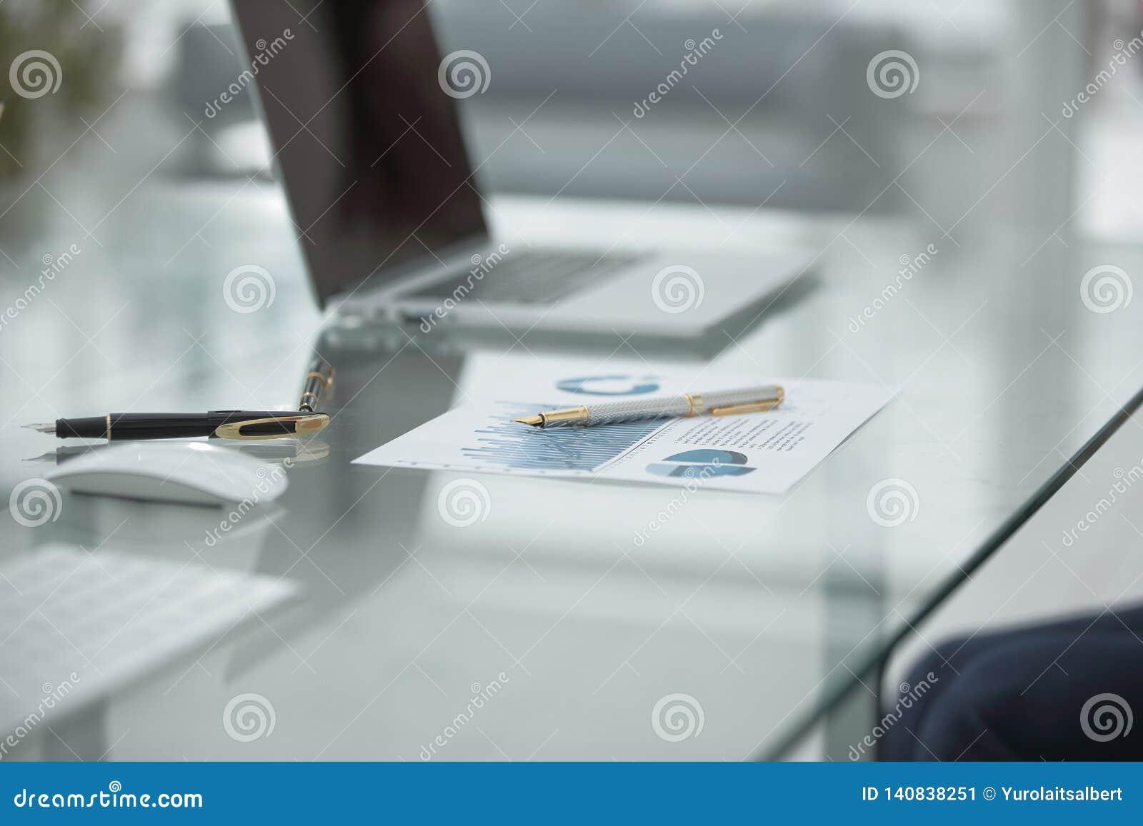 Close upp finansiellt schema och pennor på tabellen på affärsmannen