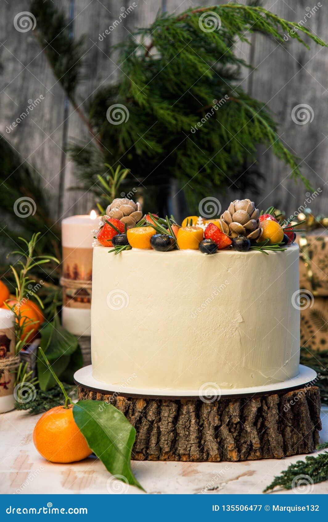 Close upp Nytt års kaka, dekorerade olika bär Grå träbakgrund, junipesfilialer