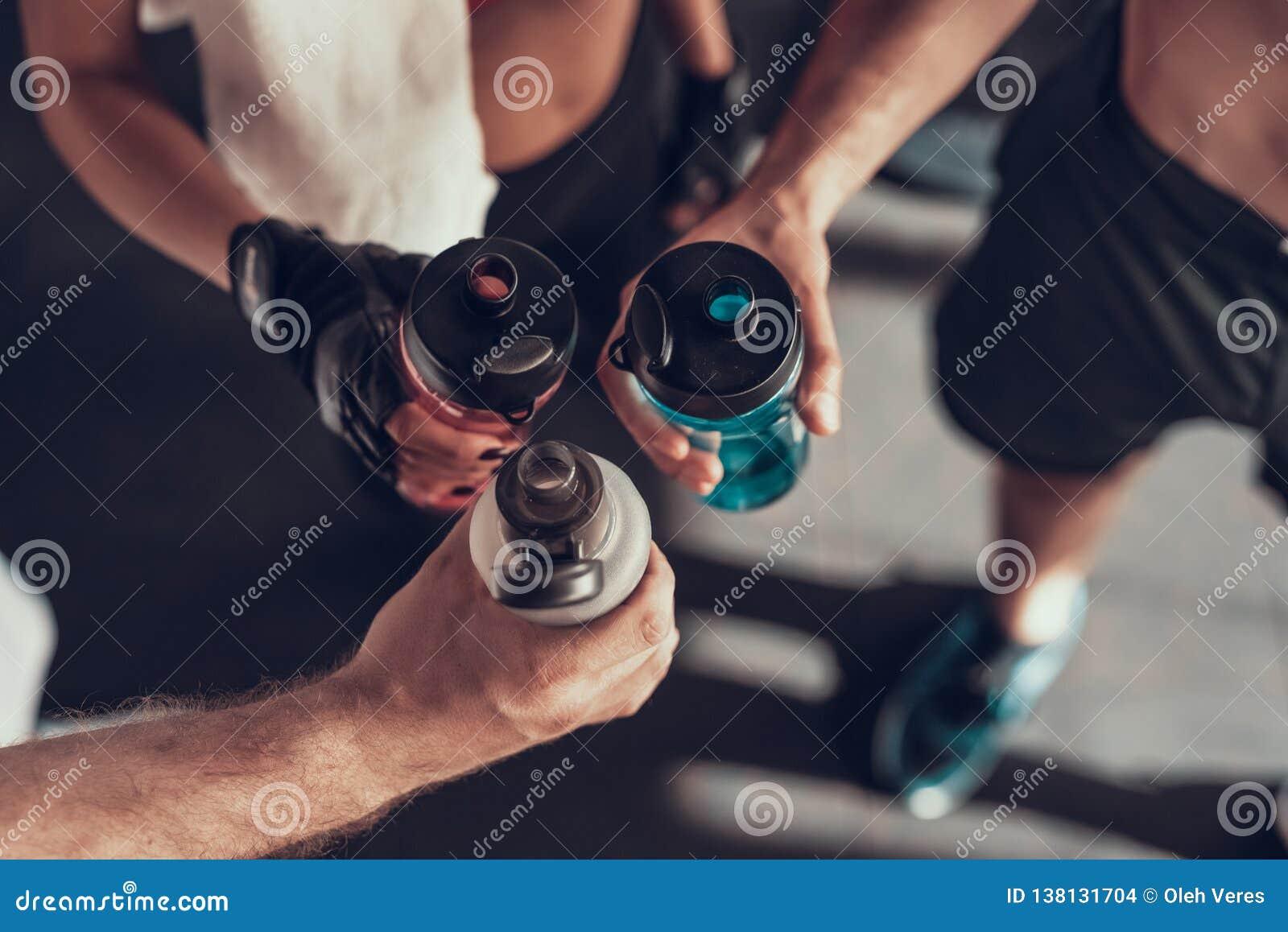 Close upp Tre händer med flaskor i idrottshallen