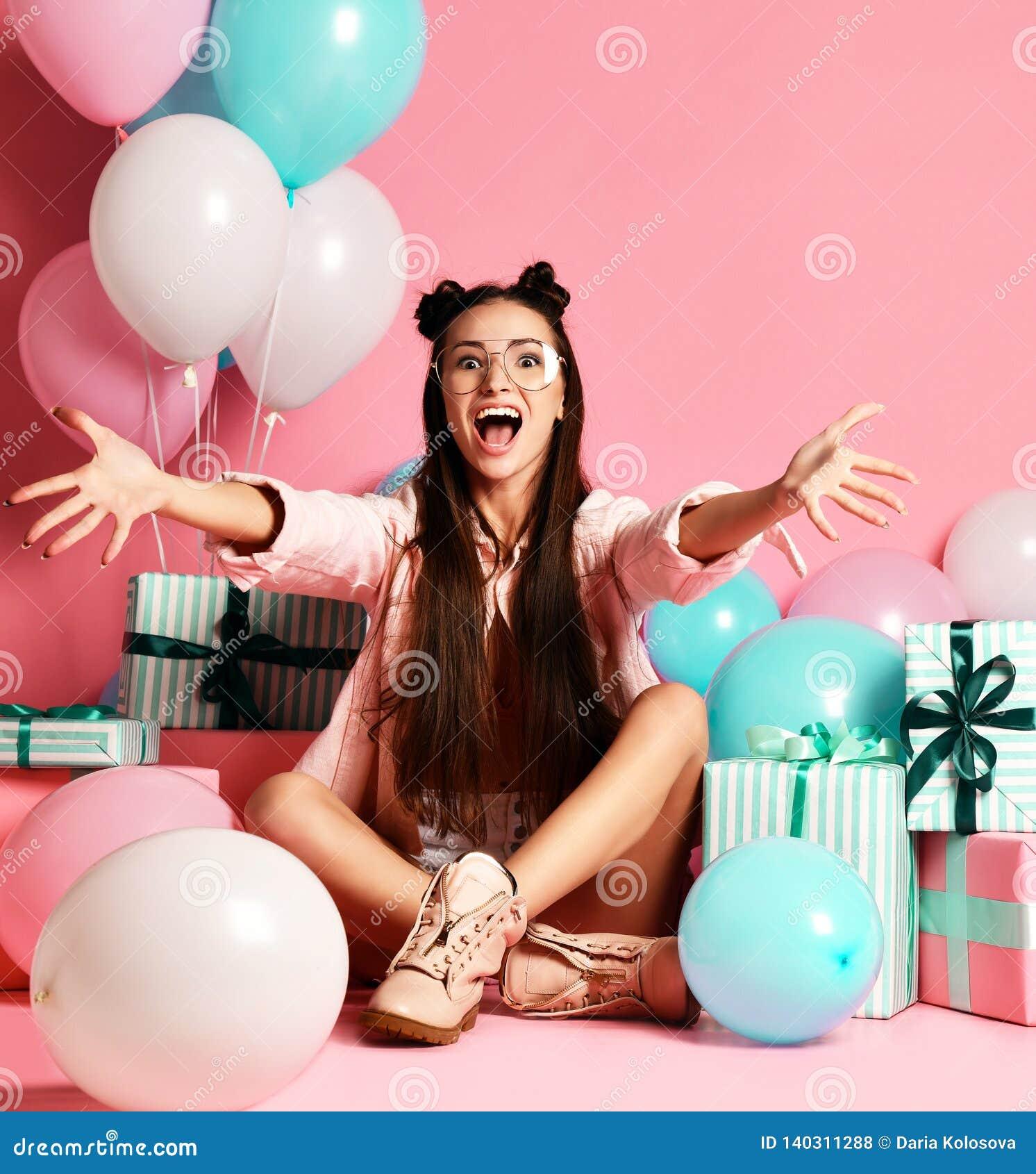 Close-upportret van aantrekkelijk meisje met heden en ballons voor studio